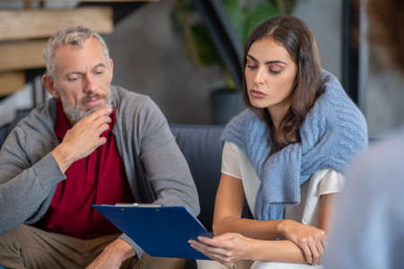 After therapy. A man and woman checking their therapist report