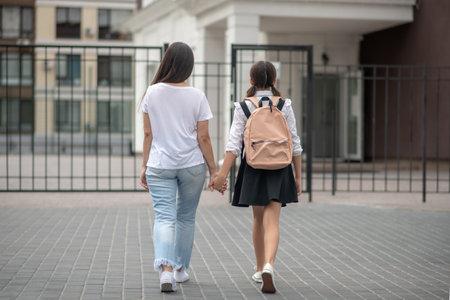 Back to school. Woman in jeans with schoolgirl in school uniform walking by arm to school, view from back Stock fotó