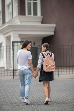 School. Mom and daughter coming up to school gate together holding hands communicating happy