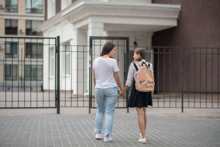 Escort to school. Mom in tshirt and jeans with daughter in school uniform standing in front of school gate smiling talking