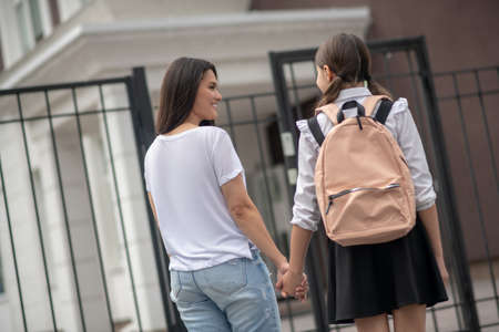 School gates. Smiling long-haired woman with schoolgirl with backpack in front of school gate in morning