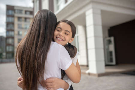 Native people. Smiling happy schoolgirl girl with closed eyes hugging long haired mom near school on sunny morning