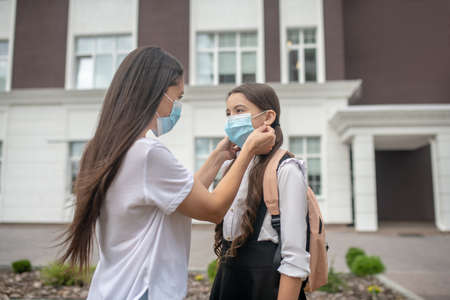 Means of protection. Caring mother putting on protective mask for her daughter schoolgirl standing in schoolyard