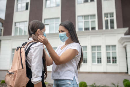 Personal protective equipment. Long-haired woman and schoolgirl with backpack wearing protective masks standing in front of school