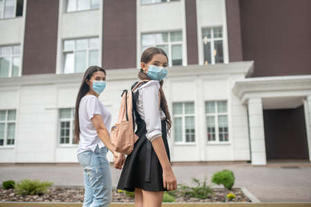 Safety regulations. Mom and daughter in school uniform in protective masks walking holding hands to school