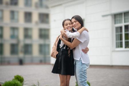Happy people. Mom and daughter schoolgirl with backpack happy smiling embracing standing in schoolyard