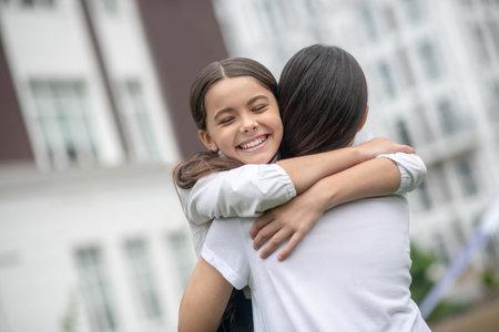 Welcome, hugs. Mom in white blouse with her back to the camera hugging happy schoolgirl daughter in schoolyard Stock fotó