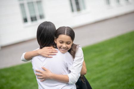 Hugs, emotions. Smiling school age girl with closed eyes hugging mom tightly in schoolyard Stock fotó