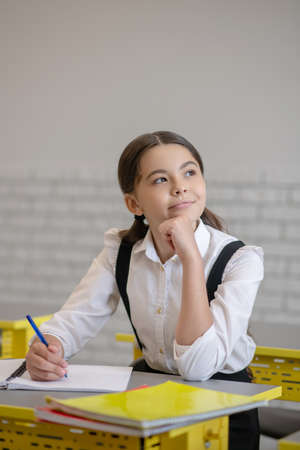 Thoughtfulness. Pensive schoolgirl with long dark hair with pen in her hand at desk looking to side