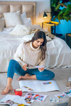 Wishlist. Cute young woman cutting pistures from magazines and making a wishlist