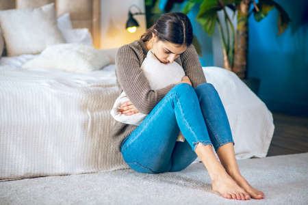 Unhappy. Young woman huging her pillow and looking unhappy