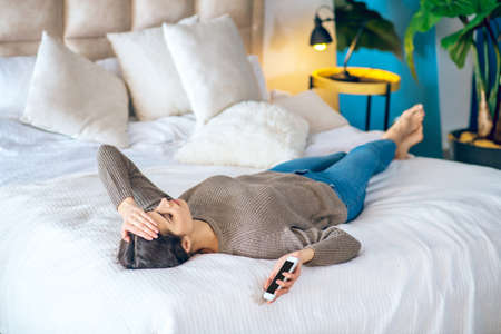 Break up. Dark-haired young woman lying on bed with a phone in her hand and looking unhappy Imagens