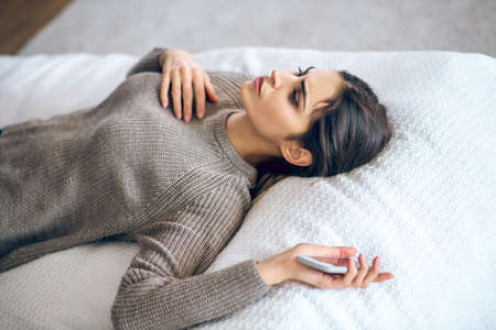 Frustration. Dark-haired young woman lying on bed with a phone in her hand and looking frustrated