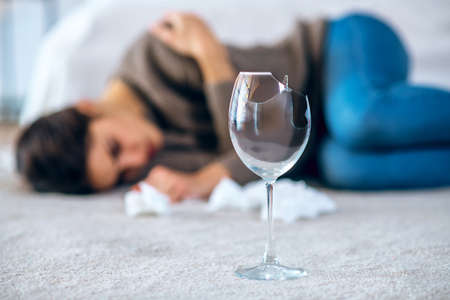 Wine. Young woman feeling depressed and drinking alcohol