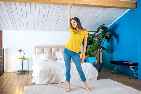 Happy girl. Long-haired beautiful young woman enjoying her time at home Imagens