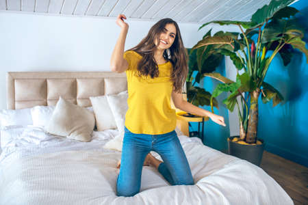 Enjoying. Long-haired beautiful young woman looking cheerful and excited