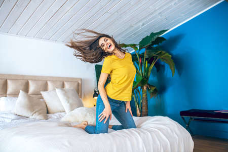 Happy woman. Long-haired beautiful young woman looking cheerful and waving her hair in the air