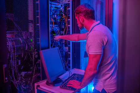 Search for problem. Male engineer in dark server room with bright blue illumination standing near computer hand near wires