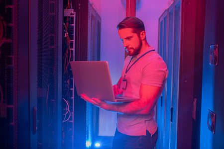 Search, information. Young bearded man with badge standing in server room with blue and red lights working on laptop Imagens