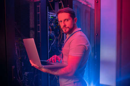 Server maintenance. Serious young bearded man standing working on laptop securing server work in blue light lit room