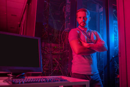 Data center. Serious young bearded man with badge in data center illuminated in red and blue