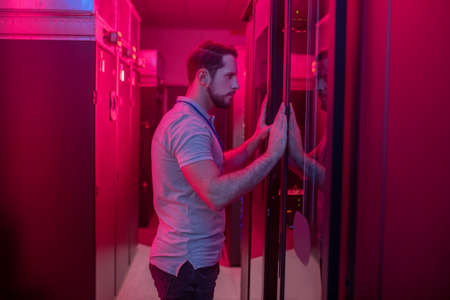 Administrator, checking. Profile of young bearded man opening wardrobe in data center with pink lighting Imagens
