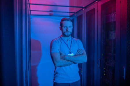Professionalism. Calm young bearded man with badge standing in datacenter with arms folded on chest illuminated by blue light Imagens