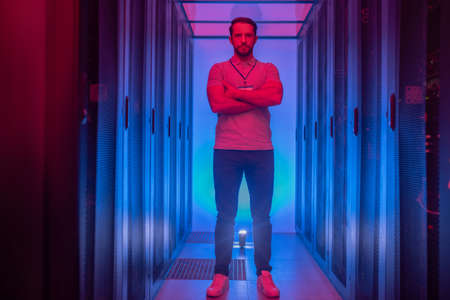Lucky day. Confident young adult programmer with arms folded on chest standing in data center with glowing blue and red