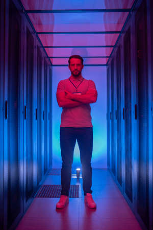 Good mood, work. Muscular young adult man in tshirt and jeans standing posing near server racks in blue red lighting