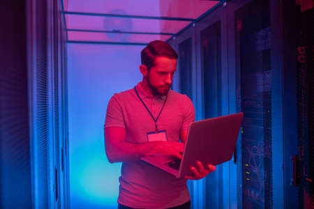 Search, information. Young man system administrator with badge standing in datacenter with blue and red lights working on laptop