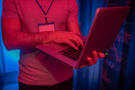 Work, responsibility. Male strong hands holding open laptop in data center face not visible