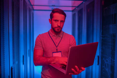 Server. Serious young bearded man standing working on laptop securing server work in dark room with blue backlight