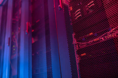 Powerful server. Server rack enclosed by protective iron doors with many holes illuminated by blue and red light