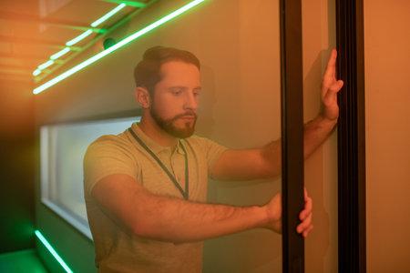 Glass transparent door. Serious young adult man leaving room opening transparent glass door at work Imagens