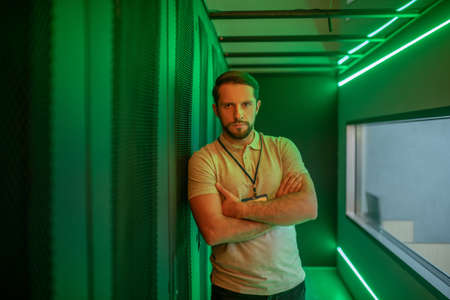 Minute of reflection. Young adult bearded man with badge standing leaning on server cabinet thinking hands folded Imagens