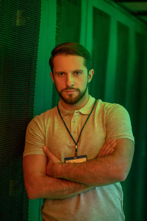 Confidence. Calm muscular young bearded man with badge standing in datacenter with arms folded on chest illuminated by green light