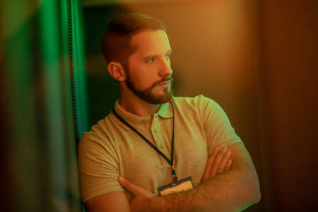 Observation. Pensive attractive young bearded man calmly looking to the side indoors with green yellow light