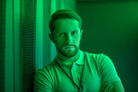 Responsibility, reliability. Confident handsome bearded man looking straight at camera standing indoors illuminated by green light