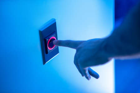 Start button. Hand approaching round button on wall in room with glowing blue light