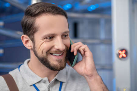 Good news. Close up smiling face of happy young adult man talking on smartphone Imagens
