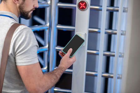 Ingress protection. Bearded young man applying smartphone to access scanner at turnstile of entrance organization