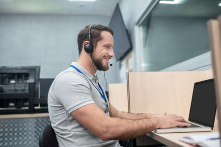Dispatcher, information. Attractive bearded young man in headphones with microphone working at computer in office