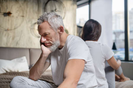 Misfortune, relationship. Unhappy gray-haired bearded man with his head resting on hand sitting back to back of woman at home