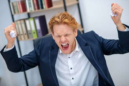 Stress at work. Angry screaming redhaired young man with closed eyes and raised fists in business suit at office Stock Photo
