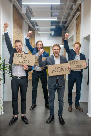 Unemployment. Group of emotional young adult men in business clothes standing with placards with raised fists in office