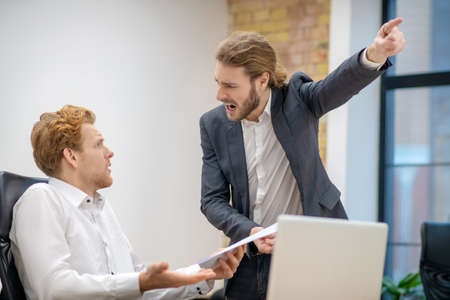 Work, nerves. Screaming angry man pointing away and bewildered scared colleague sitting at laptop