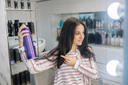 Hair styling. Long-haired young brunette spreading some hair spray on her hair