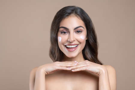 Excellent care product. Young beautiful woman with shoulders and cream on cheeks in joyful mood
