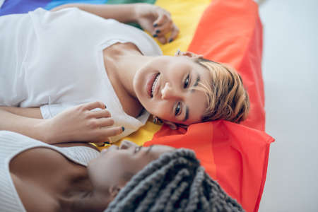 Relaxed. Two young girls with a rainbow flag lying on the floor
