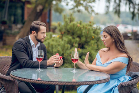 Proposal, renouncement. Serious young bearded man in suit giving ring and pretty woman in festive dress refusing sitting in outdoor cafe